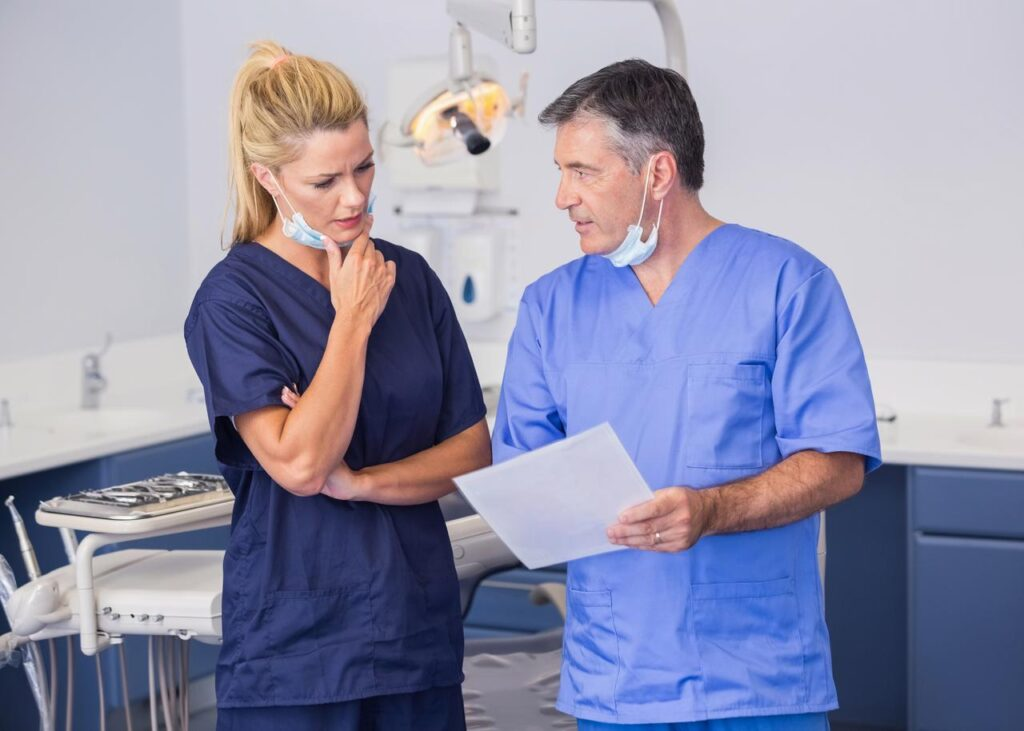 Dentist Discussing With The Nurse On Some Notes