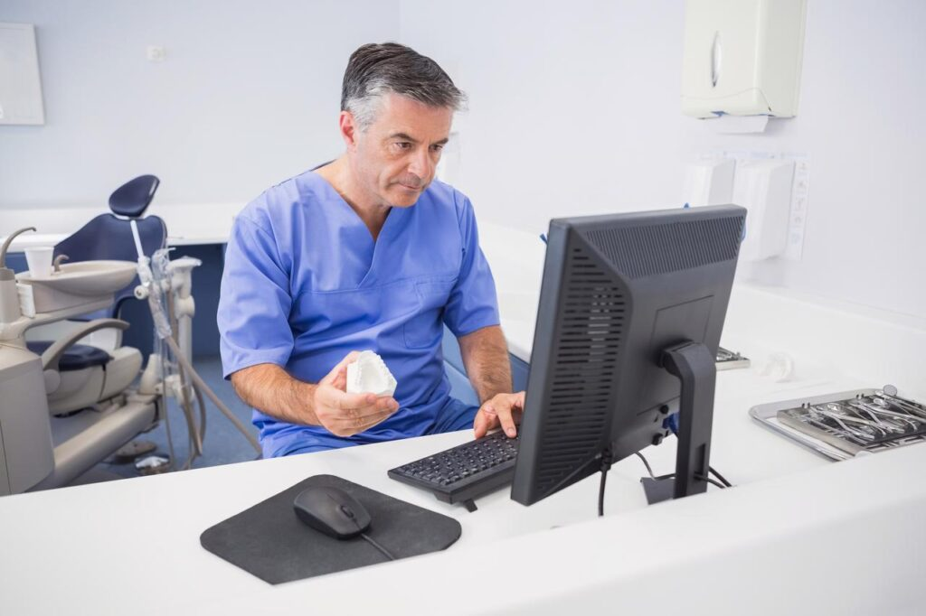 Dentist Holding Typodent And Using Desktop Computer