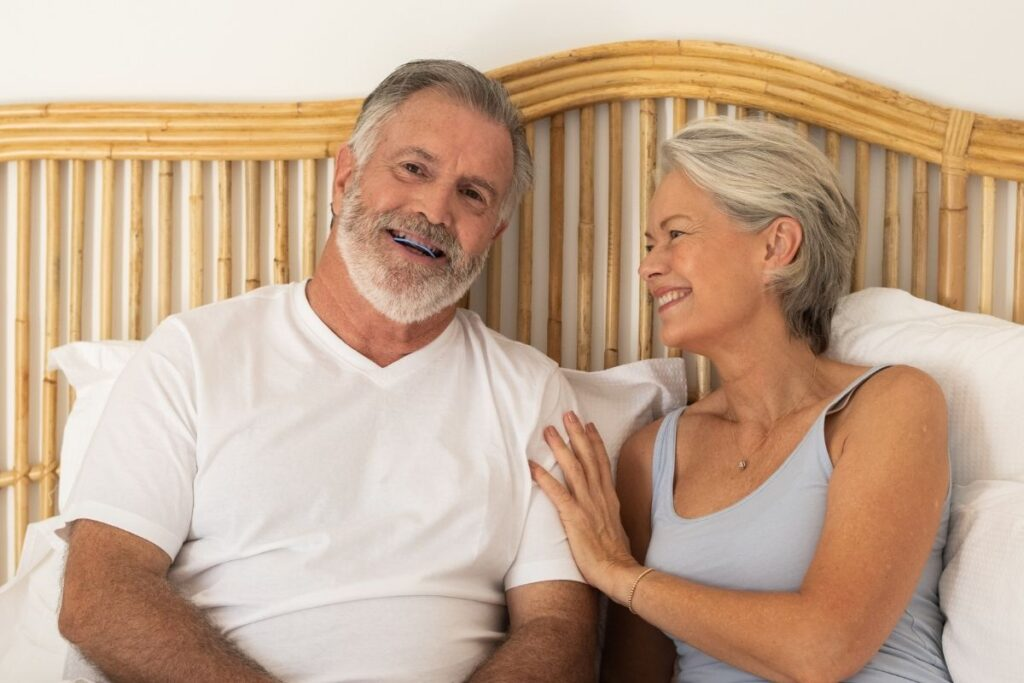 Husband smiling with SomnoDent Avant and wife looking on happily image