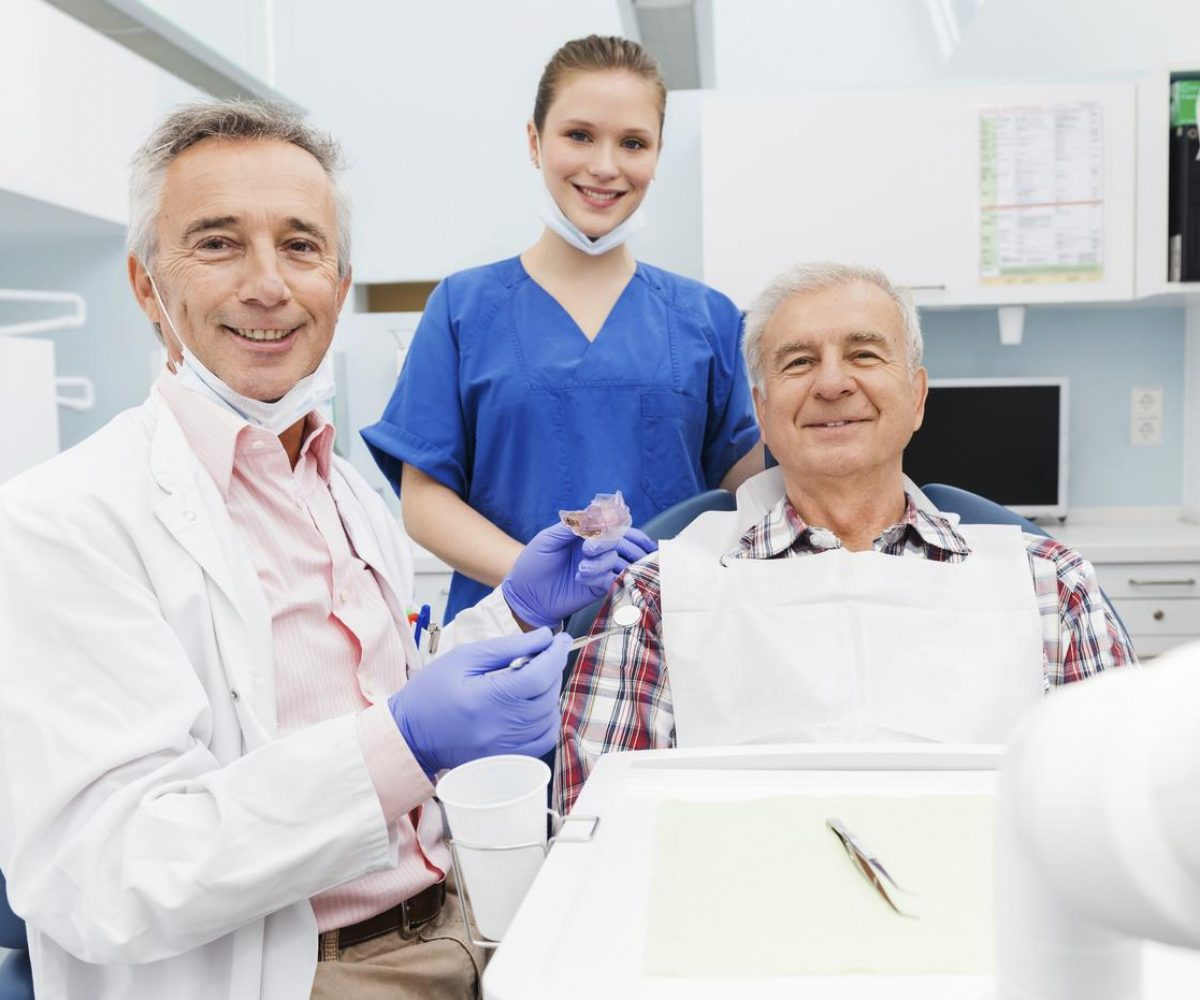 Dentist Fitting Patient With SomnoDent Fusion