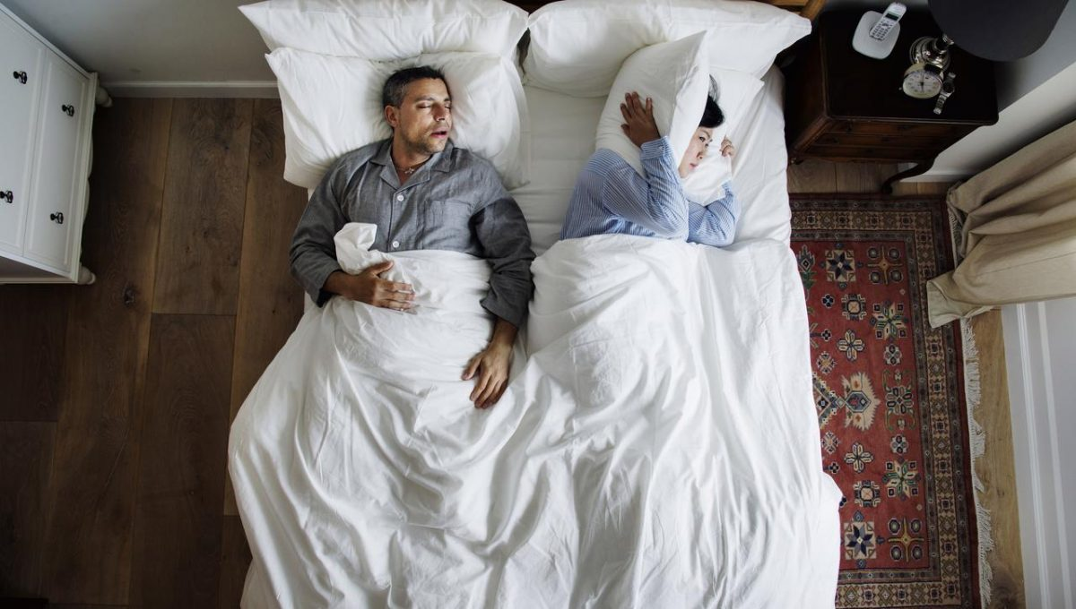 Man snoring and woman holding pillow to hear ears 2