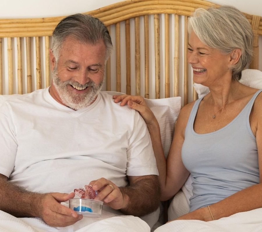 Happy couple in bed smiling at SomnoMed oral device